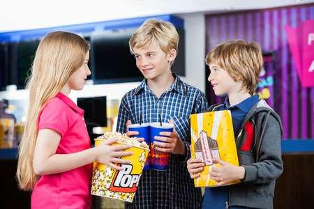 theater popcorn: Happy siblings talking while holding popcorns and drinks at cinema