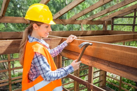 timber frame: Smiling Female Worker Hammering Nail On Timber Frame