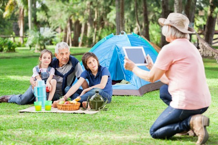 Grandmother Photographing Family At Campsite photo