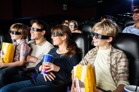 3d: Smiling Families Watching 3D Movie In Theater Stock Photo