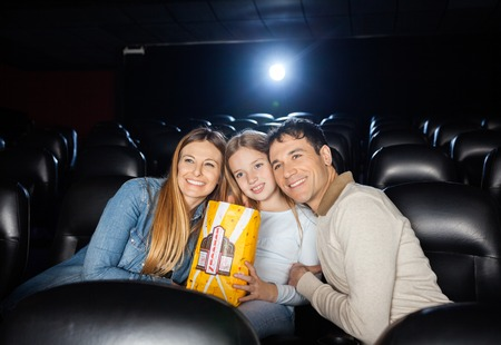 affectionate actions: Happy Family Watching Film In Theater