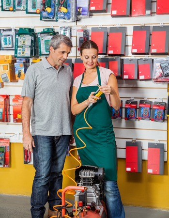 compressed air hose: Saleswoman Explaining Air Compressor To Customer In Store