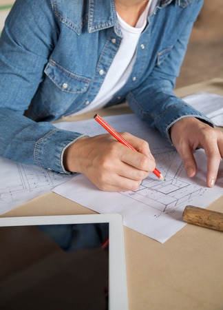 midsection: Midsection Of Female Carpenter Working On Blueprint Stock Photo