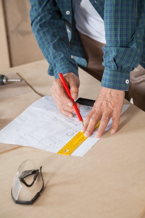 midsection: Midsection Of Carpenter Drawing Blueprint At Table Stock Photo