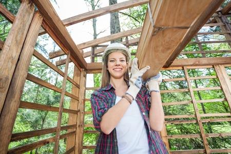materiales de construccion: Confiado Mujer Trabajador que lleva tablones de madera