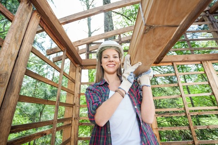 site construction: Confident Female Worker Carrying Wooden Planks Stock Photo