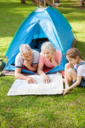 staycation: Grandparents With Granddaughter Studying Map At Campsite Stock Photo