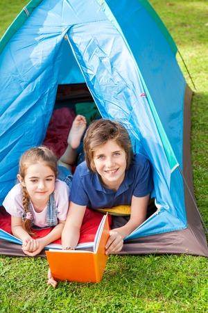 staycation: Happy Boy With Sister Reading Book In Tent
