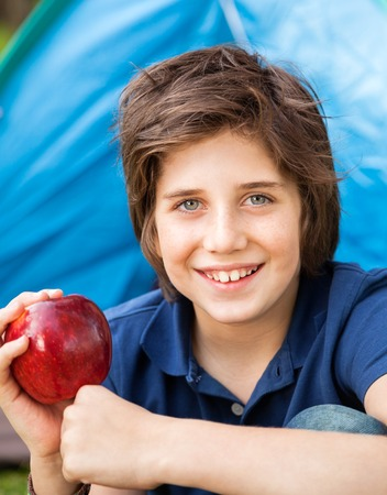 staycation: Boy Holding Apple At Campsite