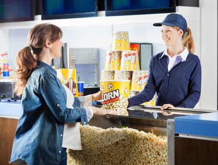 concession: Pregnant Woman Buying Popcorn At Cinema Concession Stand Stock Photo