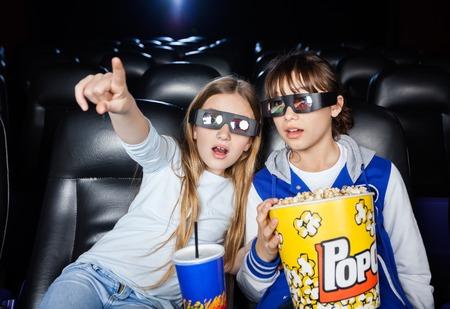 palomitas de maiz: Chica mostrando algo a la hermana en el teatro 3D