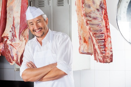 meat counter: Happy Butcher With Arms Crossed In Slaughterhouse