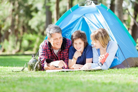 staycation: Family Studying Map While Lying In Tent Stock Photo