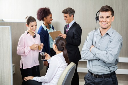 Smiling Customer Service Representative Standing Arms Crossed photo
