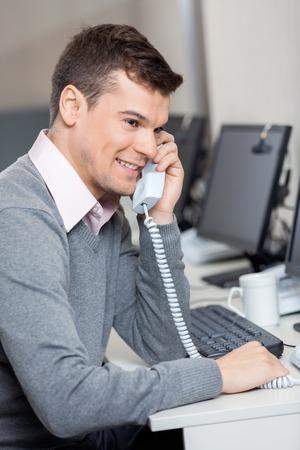 answering phone: Customer Service Representative Using Landline Phone At Desk Stock Photo
