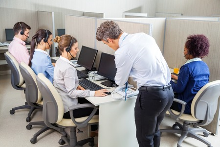 on call: Manager Assisting Customer Service Agent In Call Center Stock Photo