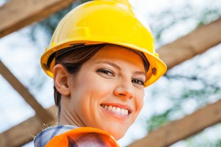 obrero trabajando: Sonrisa femenina del trabajador de construcci�n en el emplazamiento de