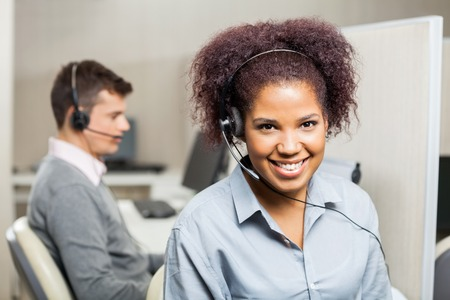 Smiling Female Customer Service Representative In Office Stock Photo