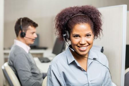 servicio al cliente: Sonriente femenino del servicio al cliente Representante En Office Foto de archivo