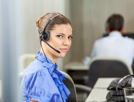 customer service representative: Portrait of confident female customer service representative wearing headset with colleague working in background at call center