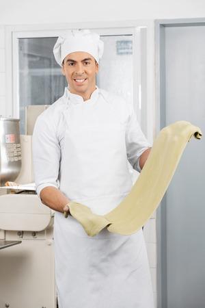 toque blanche: Smiling Chef Holding Green Spaghetti Pasta Sheet At Kitchen