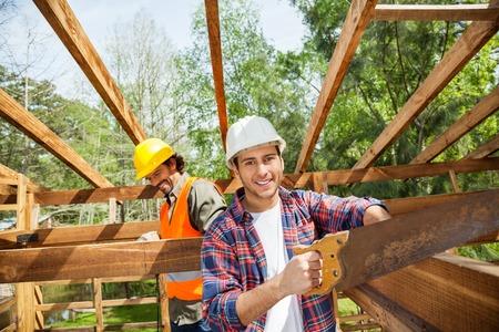 serrucho: Trabajador feliz de cortar madera con serrucho En Construcción Sitio Foto de archivo