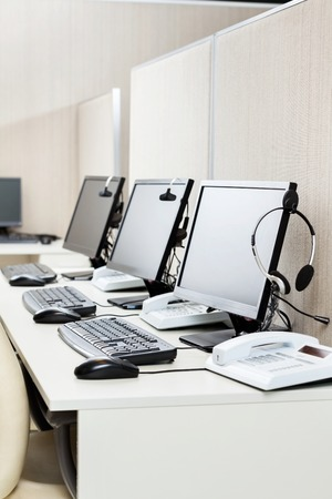 call: Computers With Headphones At Office Stock Photo