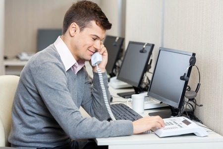 answering phone: Call Center Employee Using Landline Phone Stock Photo