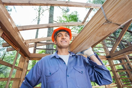 Smiling Construction Worker Carrying Wooden Planks photo
