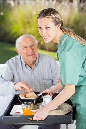 home care: Portrait Of Smiling Female Nurse Serving Breakfast To Senior Man Stock Photo
