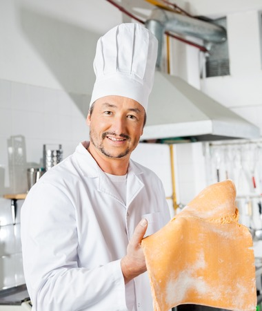 Happy Chef Holding Ravioli Pasta Sheet In Kitchen Stock Photo