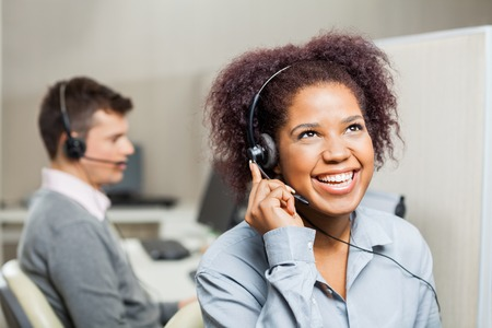 customer service representative: Cheerful Female Customer Service Representative In Office Stock Photo