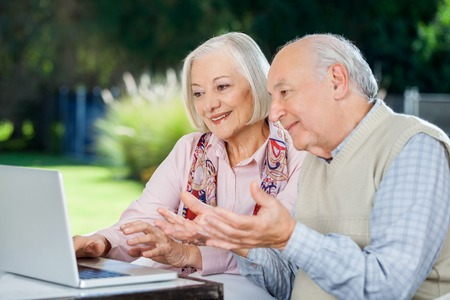 female senior adults: Elderly Couple Video Chatting On Laptop Stock Photo