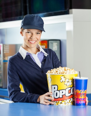 concession: Smiling Worker With Popcorn And Drink At Concession Stand
