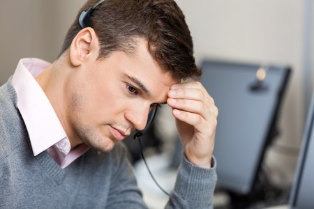 frustrated man: Tensed Customer Service Representative In Call Center Stock Photo