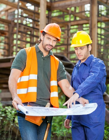 Confident Architect With Colleague Analyzing Blueprint At Constr photo