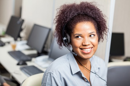 telephone headsets: Customer Service Representative Working In Office Stock Photo