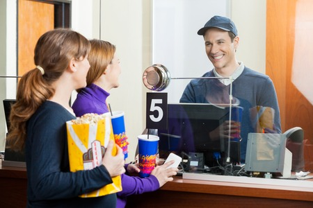 Women Buying Movie Tickets From Seller At Box Office Stock Photo