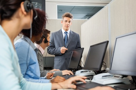 servicio al cliente: Gerente Instruir los representantes del Servicio al Cliente En Oficina Foto de archivo