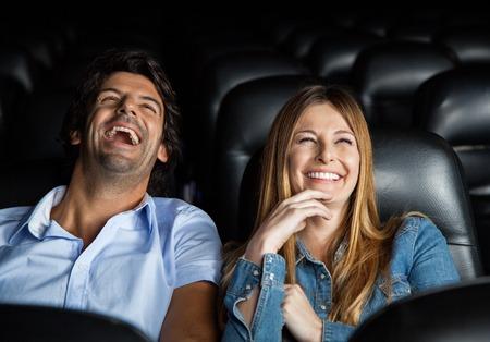 Paar lachen tijdens het kijken naar de film In Theater Stockfoto