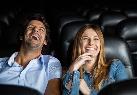 riendo: Pareja riendo mientras ve la película En Teatro
