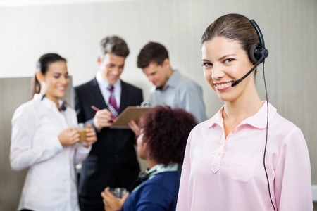 center agent: Happy Female Service Agent Standing At Call Center