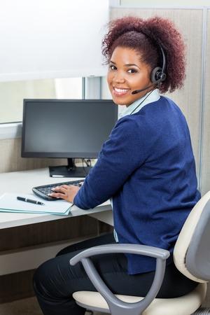 幸せな女性の顧客サービスの幹部はコンピューターを使用して