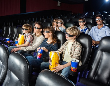 watching movie: Families Watching 3D Movie In Cinema Theater