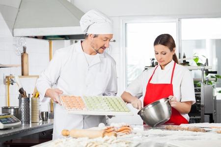 toque blanche: Chefs Preparing Ravioli Pasta At Kitchen Counter