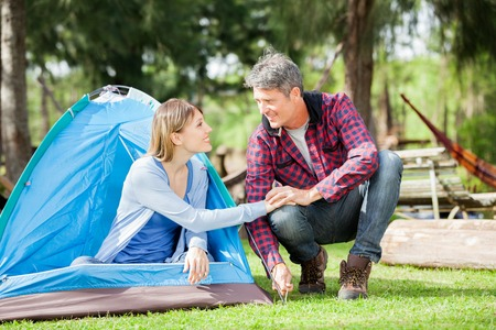 Couple Holding Hands While Setting Up Tent In Park photo
