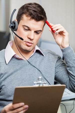 confundido: Confundido Servicio al Cliente Representante sostienen el sujetapapeles