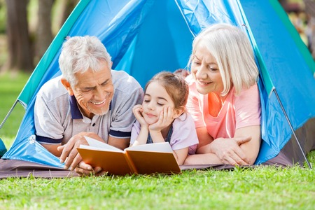 staycation: Grandparent With Granddaughter Reading Book At Campsite Stock Photo