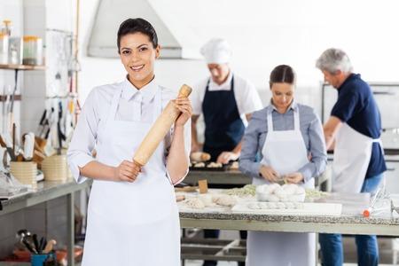 cocinas industriales: Cocinero de sexo femenino Holding Palo de amasar bien Colegas Preparación Pasta Foto de archivo