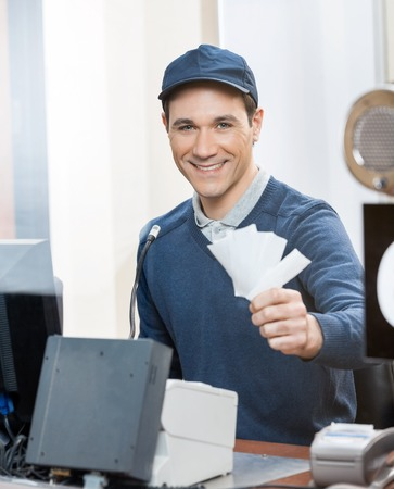 selling service smile: Worker Holding Tickets At Box Office Counter